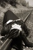 Young gothic girl lie on a railway (sepia)