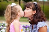 Mother is kissing daughter in a park