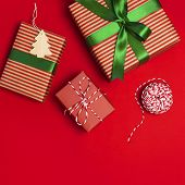 Gift Boxes With Green Ribbon On Red Background Top View Flat Lay. Holiday Concept, New Year Or Chris poster