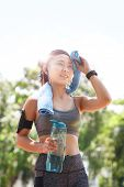 From Below Of Young Asian Sportswoman In Earphones Holding Towel And Wiping Forehead With Towel In S poster