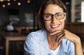 Portrait of happy mature woman wearing eyeglasses and looking at camera. Closeup face of smiling wom poster