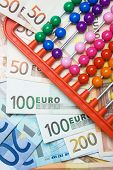 Colorful abacus beads and european paper currency