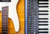A Wooden Background With A Set Of Musical Instruments Consisting Of A Keyboard And A Bass Guitar. poster
