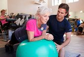 Senior Woman Exercising On Swiss Ball Being Encouraged By Personal Trainer In Gym poster