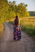 Young Boho (hippie) Girl Is Going Away By The Dirt Road In Field. Rear View. Outdoor Portrait At Sun poster