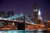 stock photo of new york skyline  - New York City Brooklyn Bridge and Manhattan skyline with skyscrapers over Hudson River illuminated with lights at dusk after sunset - JPG