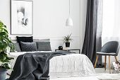 Modern, Gray Chair With Wooden Legs By A Window Of A Bright Bedroom Interior With A Dark Gray Blanke poster
