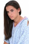 Picture of beautiful dark haired teen girl in hospital gown crying.