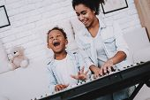 Child With Mother Play On Piano. Childhood With Mother. Hobbies With Mother. Smile Mother With Young poster