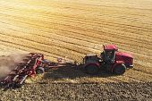 Aerial View Drone Of Harvest Field With Tractor Mows Dry Grass. Autumn Yellow Field With A Haystack  poster