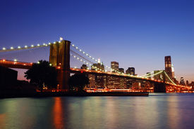 stock photo of brooklyn bridge  - New York City Brooklyn Bridge and Manhattan skyline with skyscrapers over Hudson River illuminated with lights at dusk after sunset - JPG