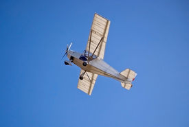 stock photo of ultralight  - A white ultralight plane flying in the blue sky - JPG