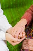 stock photo of holding hands  - A young doctor holding the hand of an old woman  - JPG