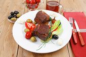 grilled meat : beef ( lamb ) garnished with tomatoes , green and black olives, tomatoes and juice on