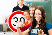 Driving school - driving instructor in his class and a female student driver looking in the Camera,