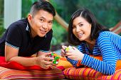 Young Indonesian couple - man and woman - at home playing with a magic cube