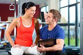 Woman with her personal fitness trainer in the gym