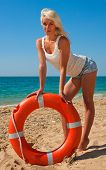 stock photo of lifeline  - Beautiful slim girl on the beach with a lifeline - JPG