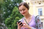 Постер, плакат: Девушка прослушивания музыки на мобильном телефоне в городе