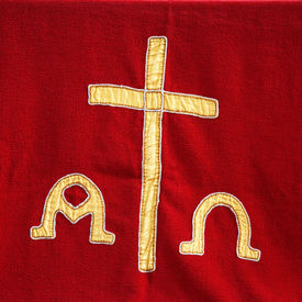 picture of ecclesiastical clothing  - Decorative symbolic gold needlework on a priests vestment or church cloth with a gold cross and religious icons on a red background - JPG