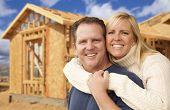 Happy Excited Couple in Front of Their New Home Construction Framing Site.