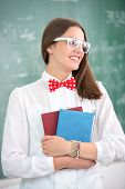 Smart schoolgirl with bowtie holding textbooks in classroom