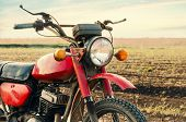 stock photo of dirt-bike  - Classic old motorcycle on a dirt road - JPG