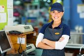 image of cashiers  - happy female hardware store cashier with arms folded - JPG