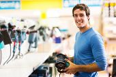 foto of hand tools  - smiling young man purchasing a hand tool in hardware shop - JPG