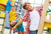 stock photo of playground  - Image of cute kids having fun on playground outdoors - JPG
