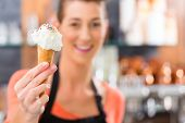 picture of ice cream parlor  - Young saleswoman in an ice cream parlor with ice cream cornet - JPG