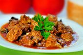stock photo of stew  - Plate with stew of pork meat on table - JPG
