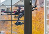 pic of drone  - A drone with a camera flying behind an opened bedroom window - JPG