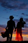 foto of western saddle  - a silhouette of a cowboy holding on to his saddle and his woman - JPG