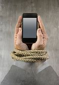foto of addiction  - Hands of businessman addicted to mobile phone rope bond wrists in smartphone internet addiction and slave to online network addict concept isolated black background - JPG
