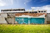 picture of old stone fence  - Abandoned factory behind old brick fence on a sunny day - JPG