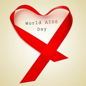 pic of hiv  - a red ribbon forming a heart and the text world AIDS day on a beige background - JPG