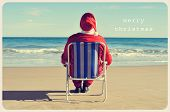picture of christmas claus  - a picture of santa claus sitting in a beach chair on the beach and the text merry christmas like a postcard - JPG
