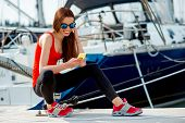 pic of marines  - Young sport woman using mobile sitting near the yachts at the marine - JPG