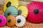 stock photo of asymmetric  - Asymmetric colourful umbrellas lying on the street - JPG