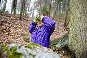 stock photo of naturalist  - Girl scout looking through the binoculars in a forest inspecting the surroundings and bird watching - JPG