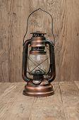 image of kerosene lamp  - kerosene lamp is on a wooden background - JPG