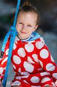 stock photo of tire swing  - Adorable little girl having fun on swing on summer day - JPG