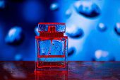 image of perfume  - Square perfume bottle on blue and red background with waterdrops - JPG