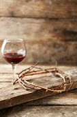 stock photo of crown-of-thorns  - Crown of thorns and glass of wine on old wooden background - JPG