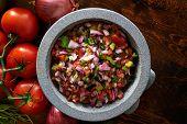 pic of condiment  - fresh mexican pico de gallo salsa in stone molcajete shot top down - JPG