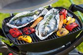 stock photo of pepper  - Fresh dorado fish and bell pepper grill cooking outdoors - JPG