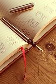 image of scribes  - Open diary with one fountain pen in it placed on a wood table - JPG