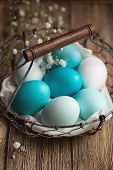 stock photo of ombres  - Dyed Easter eggs in a wire basket - JPG