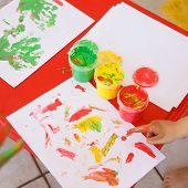image of experiments  - Child painting a drawing with finger paints used for finger drawing and sensory play - JPG